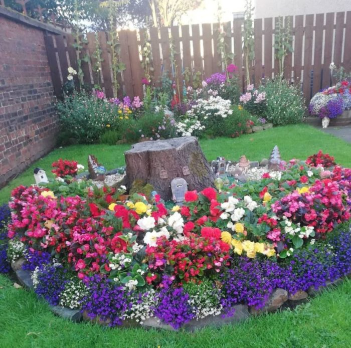 a flower bed with brightly coloured flowers and miniature fairy houses