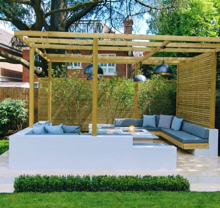a contemporary pergola with a concrete seating area and privacy screen