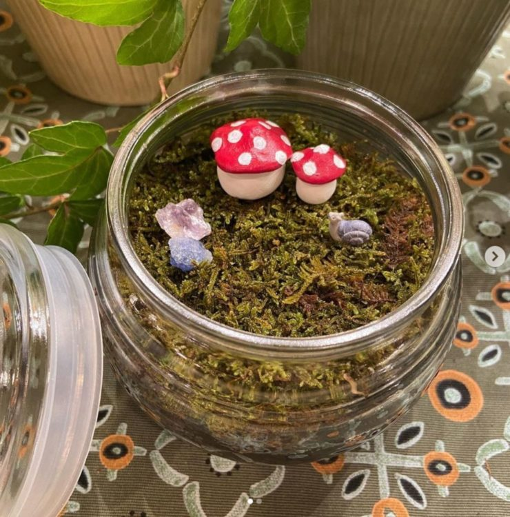 tiny toadstool sculptures on a layer of moss in a jam jar fairy garden