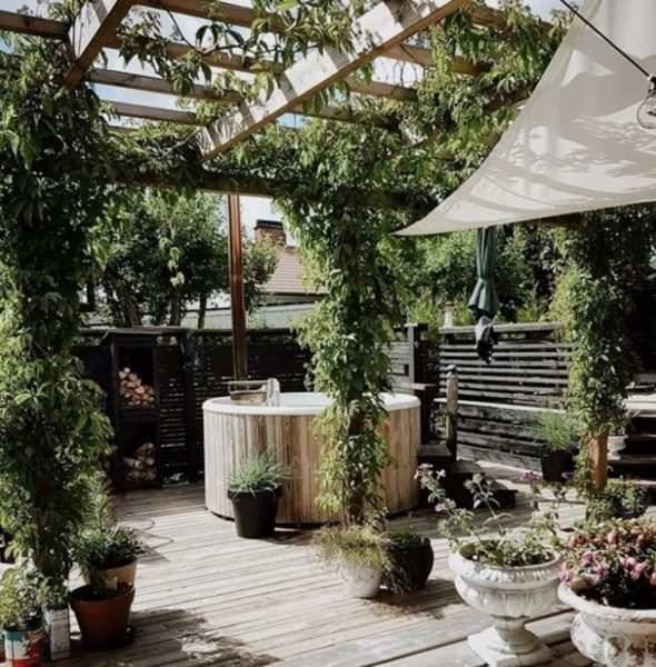 a pergola covering a deck with a hot tub in the middle, completely surrounded by plants in pots and planters, growing over the shelter