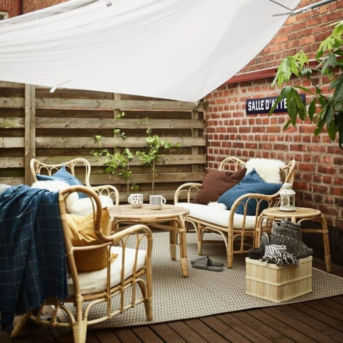a welcoming deck area with an angled canvas cover over the bamboo seating