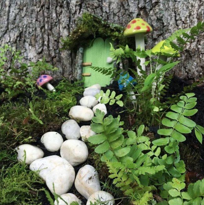 fairy garden ideas using white pebbles as a path to a miniature door