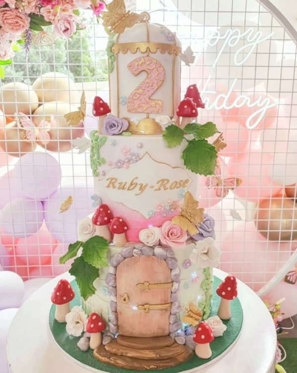 a pretty cake with three tiers, decorated to look like a fairy house