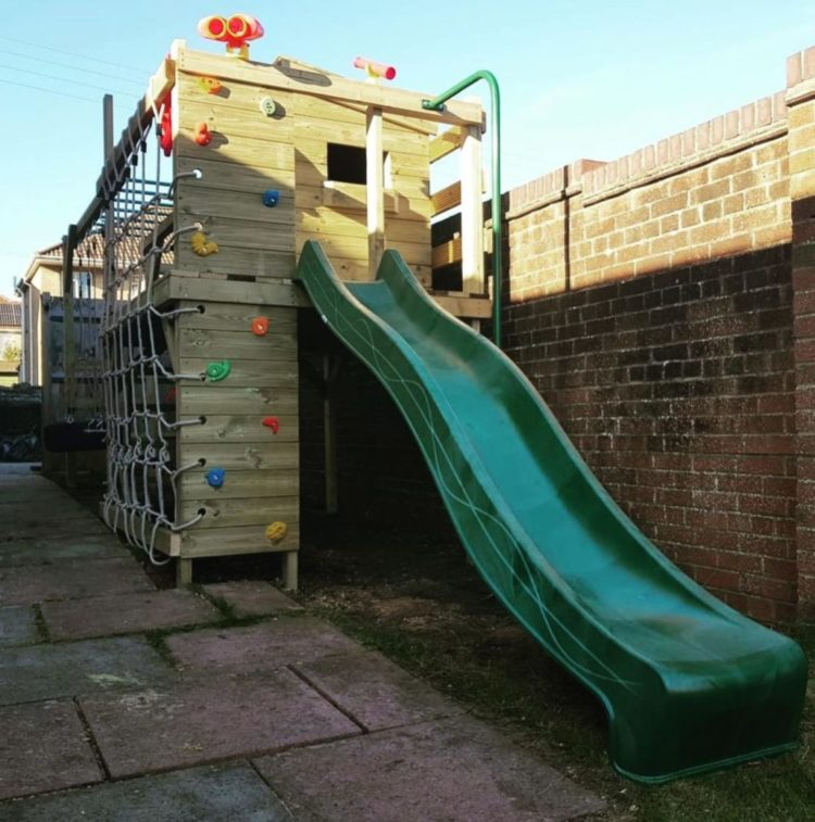a raised playhouse with a climbing wall and a slide