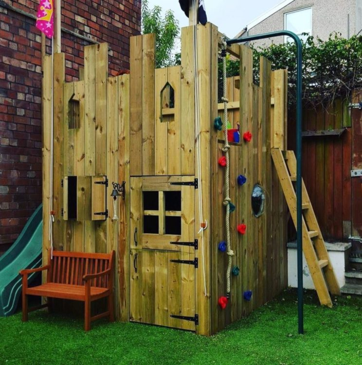 a small wooden playhouse with a ladder, climbing wall and slide