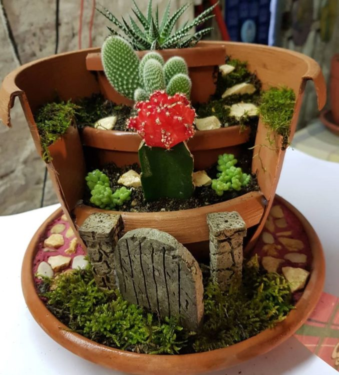 a broken pot reformed to create a fairy garden with several levels