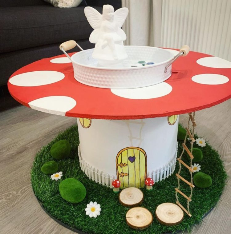 a giant cable spool has been painted to resemble a toadstool, with a miniature door, ladder and foliage