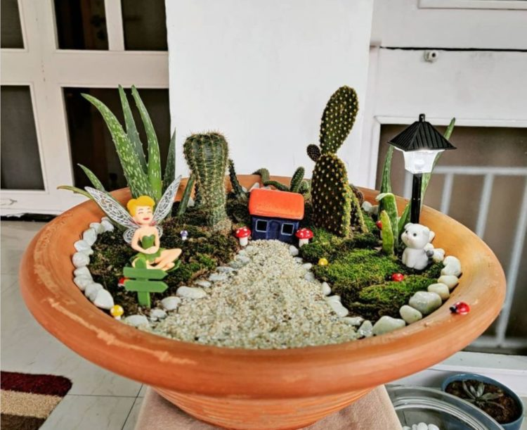 a wide terracotta pot with gravel, cacti and tiny, fairy-sized figurines
