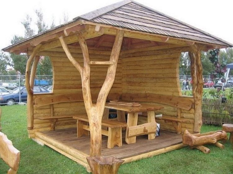 a natural wooden gazebo with supporting columns shaped like branches