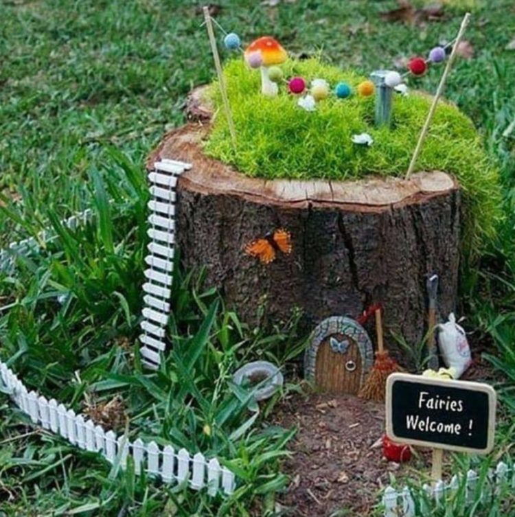 a tree stump decorated with tiny, fairy garden features