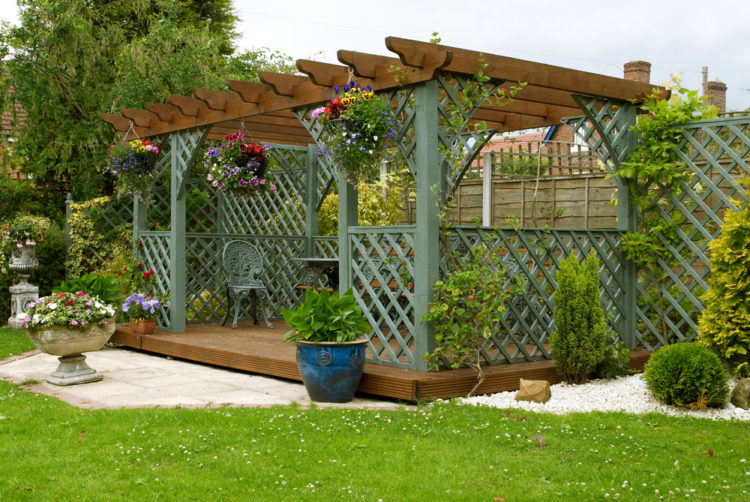 A wooden pergola with green trellis sides and a sturdy deck with garden furniture on