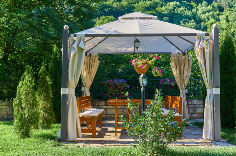 a metal-framed gazebo with luxurious canvas curtains