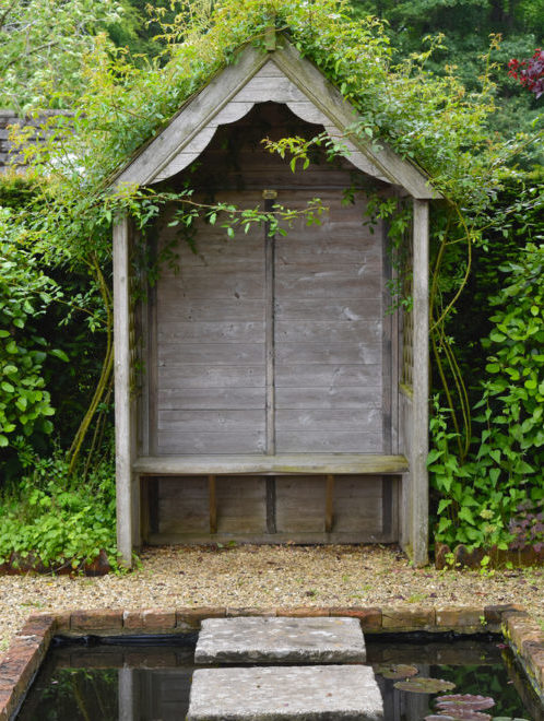 a modest wooden arbour with a solid back and scalloped roof