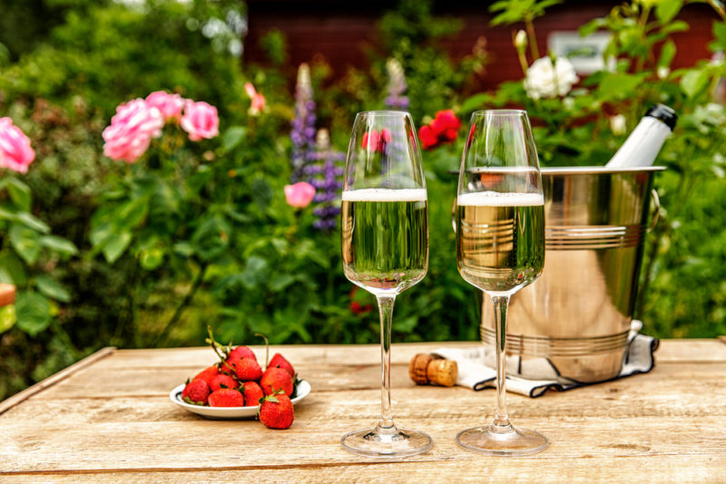 two glasses of champagne on a table next to a champagne bucket and plate of strawberries