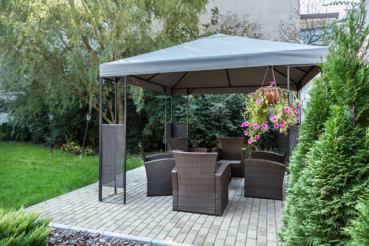 a spacious patio with a large, metal-framed gazebo over garden furniture