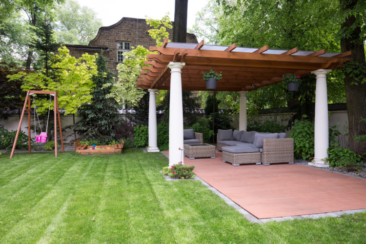 a large pergola with classical stone columns above a brick patio