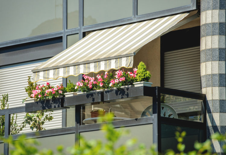 a balcony with flower boxes and a fabric awning covering for shade and privacy