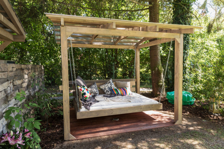 a large hanging bench in the style of a cabana