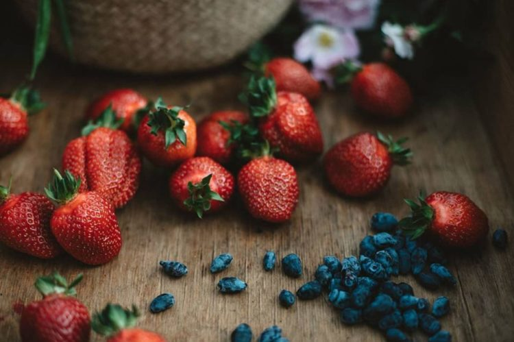an artistic close up of fresh strawberries on a wooden surface
