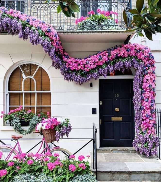 boughs of wisteria and pink flowers adorn the front of a white building in London