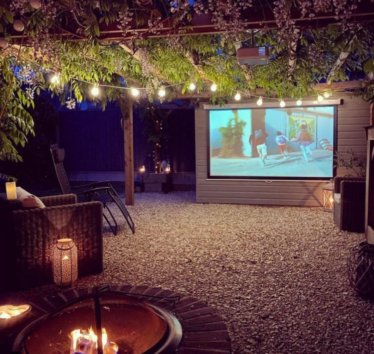 a gravelled garden with chairs under a wisteria covered pergola, facing a projector screen