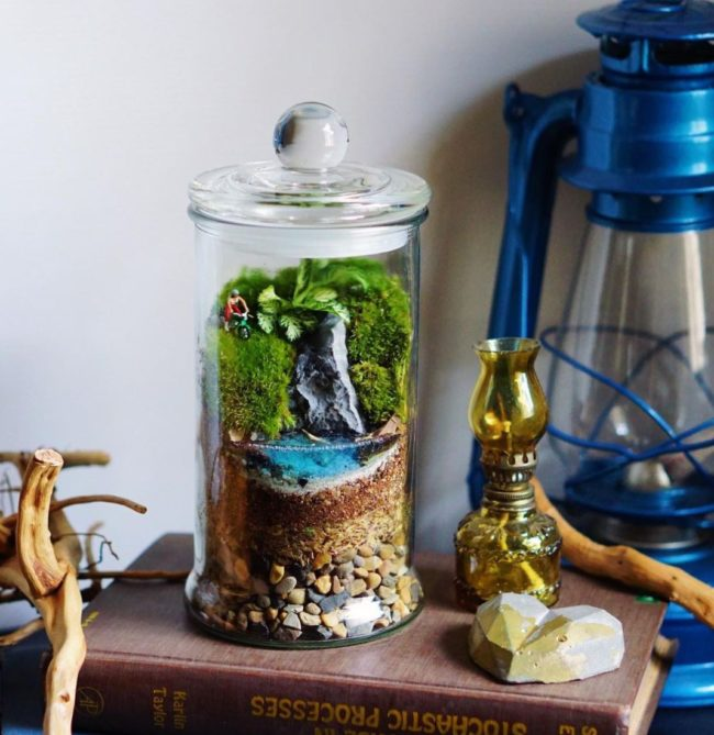 a small glass jar with sand, blue resin, green moss and a tiny figurine inside to resemble a lakeside landscape