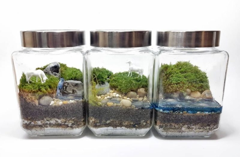 three square jars lined up to create a three-part landscape bottle garden with a resin waterfall