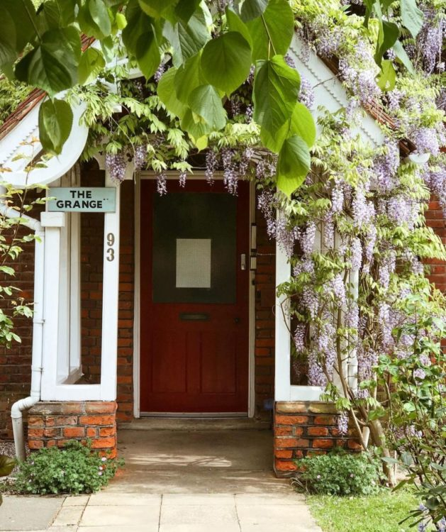 a front door is covered by a porch with wisteria growing over it