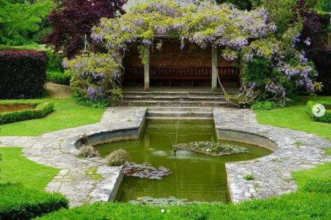 a wisteria-covered pergola overlooking a pond at Kingston Maurward Garden