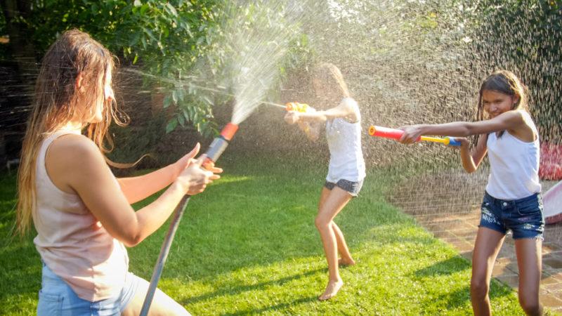 three tweenage children spraying water hoses at each other in a garden