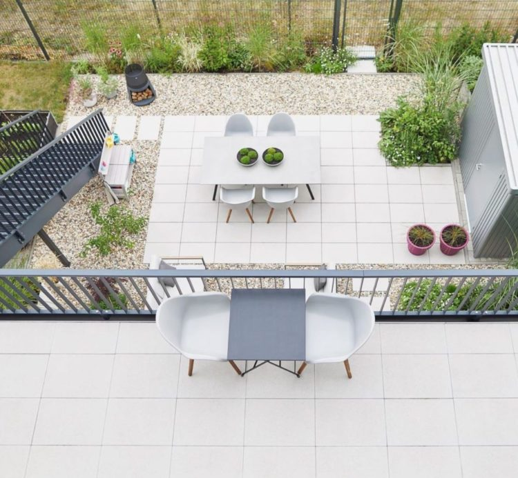 a top-down view of a balcony overlooking a patio, both with cream paving stones