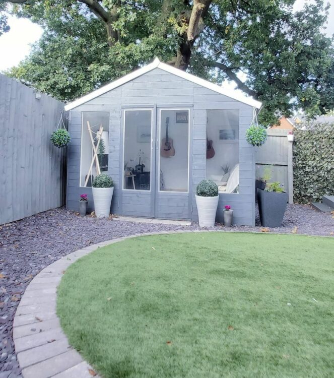 a medium sized garden cabin with windows at the front, painted a pale grey like the surrounding garden fence, with a circular lawn in front