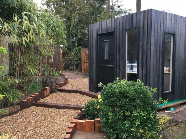 a small black garden office with black wood cladding