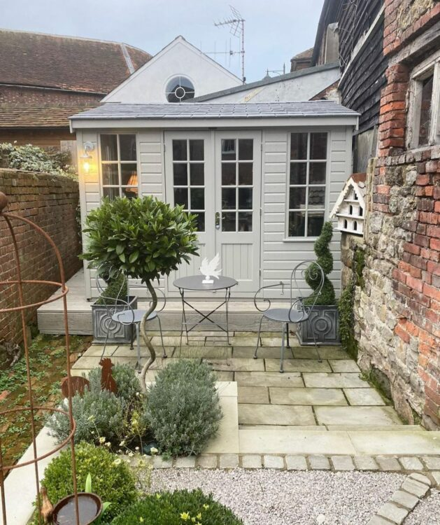 a sage green garden cabin at the back of a small garden