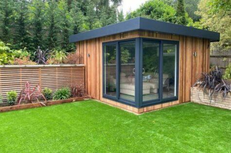 a modern, cube-shaped garden office in the corner of a garden