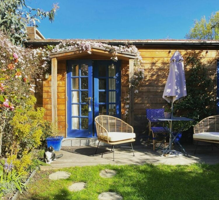 a wooden cabin with deep blue door can barely be seen behind patio furniture and a bushy clematis plant