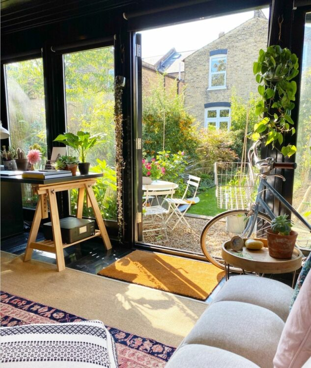 interior view of a garden office looking out - there's a sofa and desk visible
