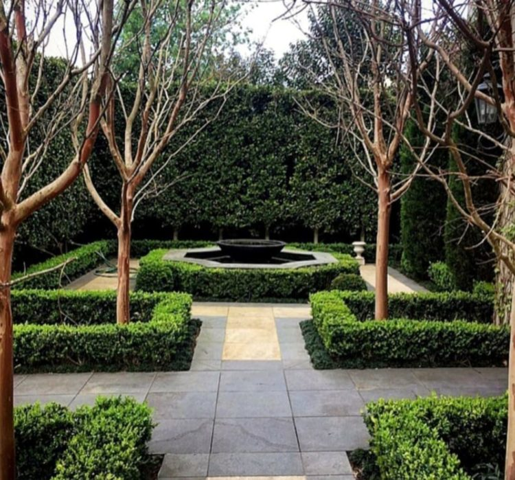 a symmetrical garden with paved flooring and shrubbery inspired by formal French gardens