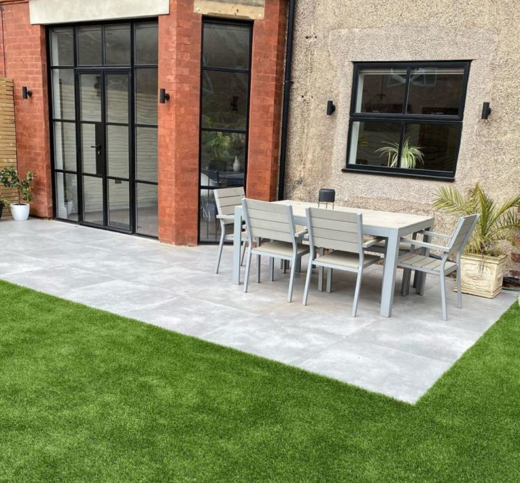a clean grey patio surrounded by a perfectly manicured lawn, outside a red brick building with industrial style windows
