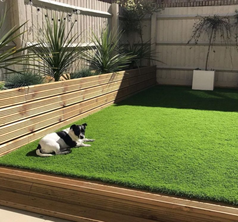 a raised lawn with a wooden boundary and a matching wooden planter at one edge