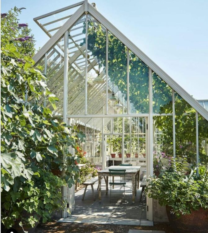 a glass orangerie or green house with a long table and chairs inside, surrounded by plants