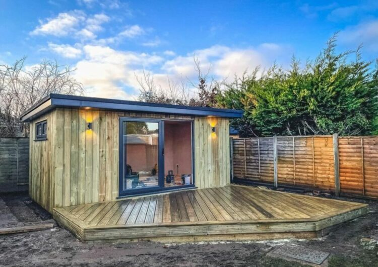 a wooden garden office with a large deck attached to the front