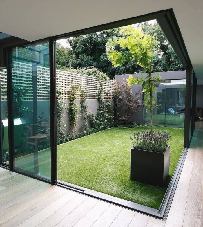 a minimalist courtyard with an artificial lawn is surrounded on three sides