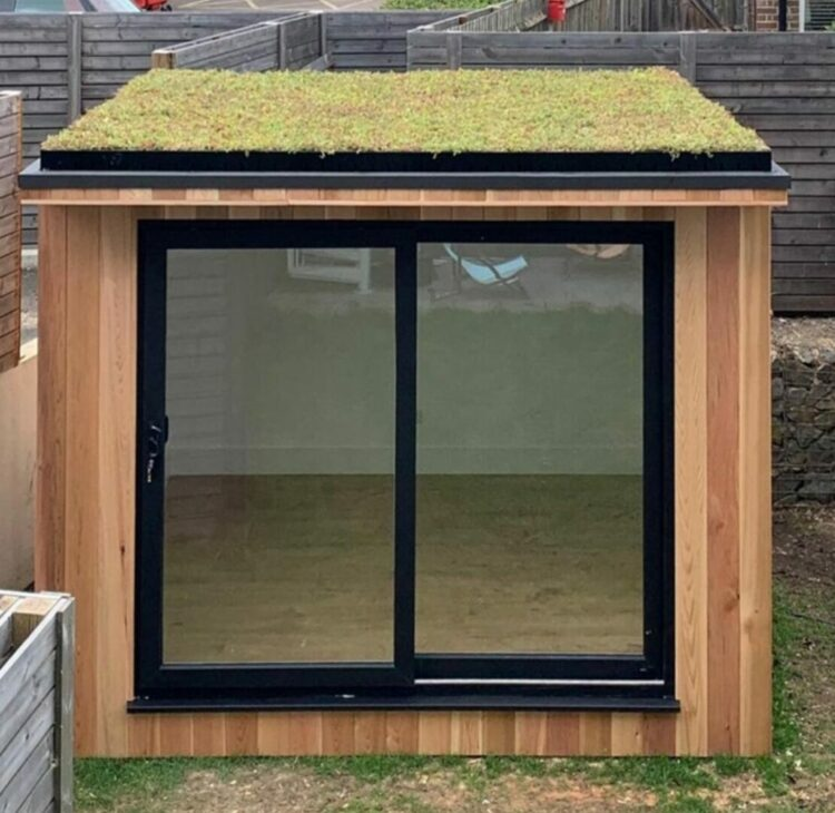 a small garden cabin with glass doors and a green roof
