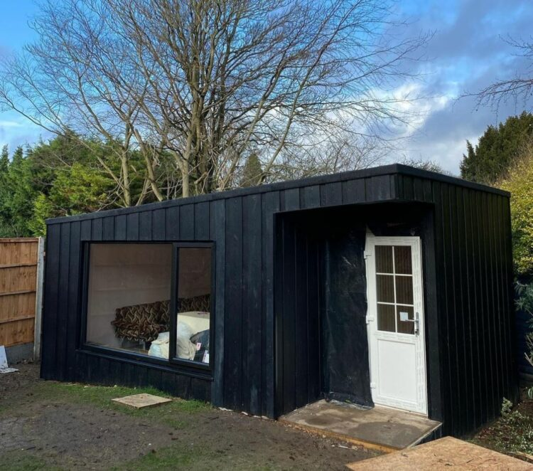 a matte black garden cabin with a large window to one side