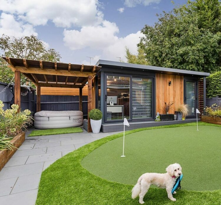 luxury garden office ideas with a putting green in front and a hot tub adjacent.