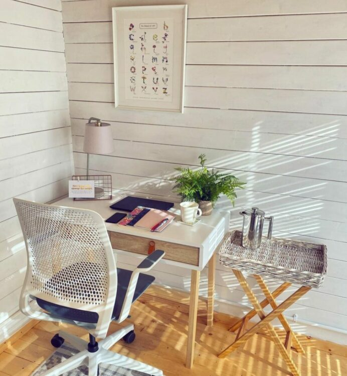 a garden office interior painted white, with a desk
