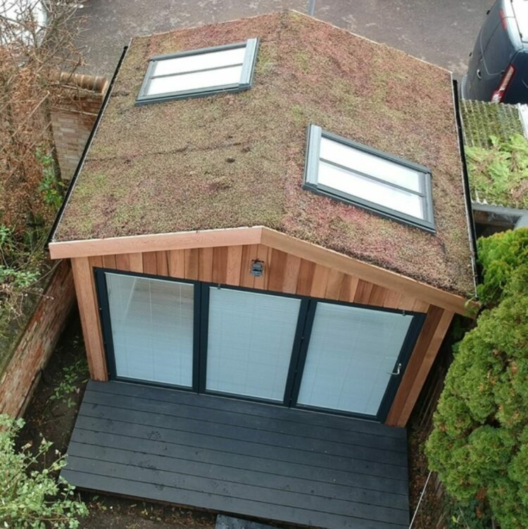 a large garden office with folding glass doors and roof windows