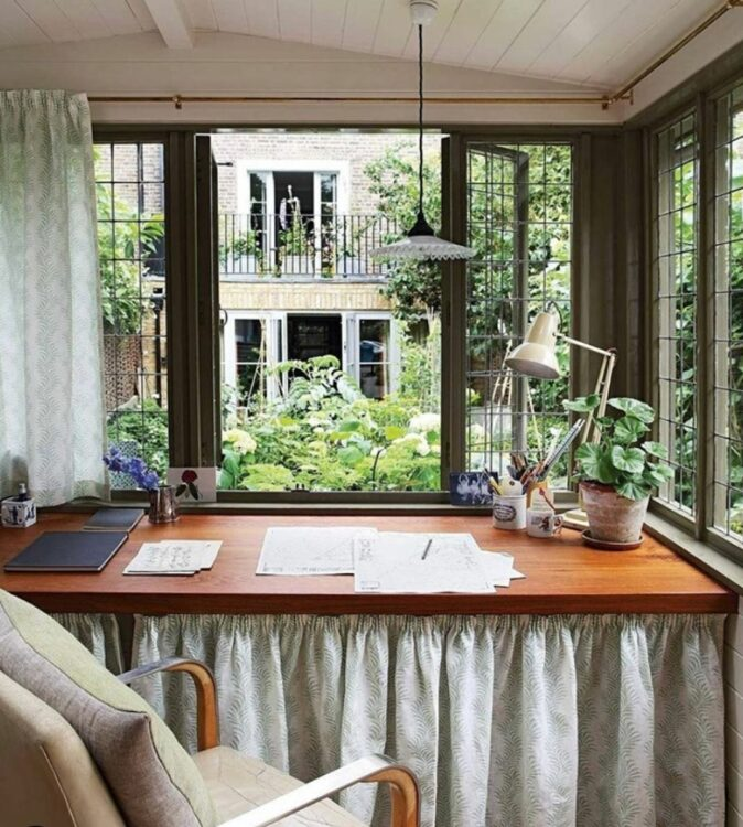 a view looking over the desk of a garden office outside, through mullioned windows dressed with pale green curtains