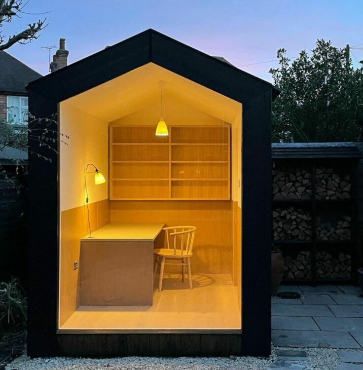 a compact garden office with one side made entirely of glass